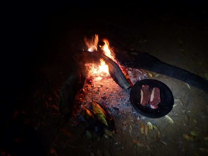 steak and corn cooking on the campfire