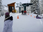 Sharni skiiing off the chair lift with instructor